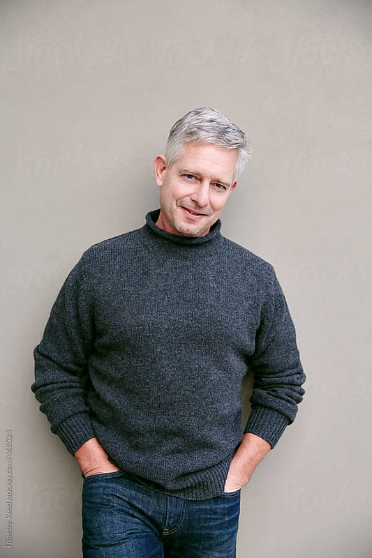 Portrait of mature man with grey hair against a grey wall by Trinette Reed for Stocksy United