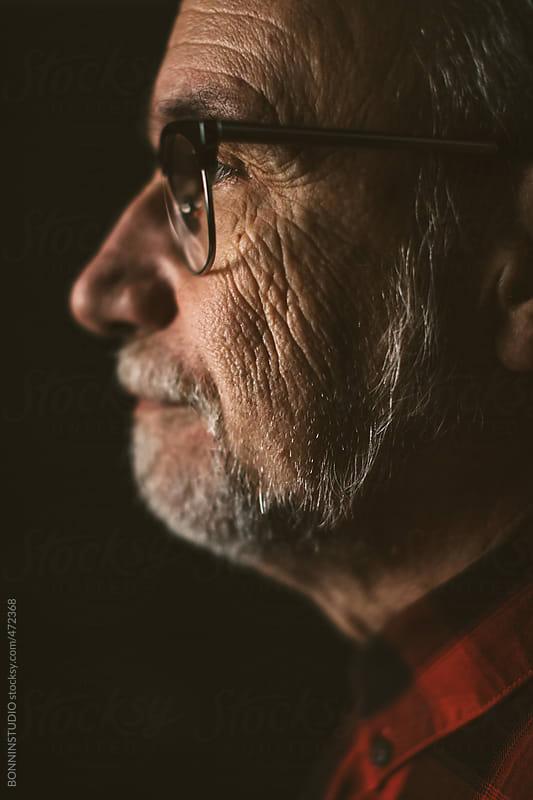 Portrait of old man on black background by BONNINSTUDIO for Stocksy United