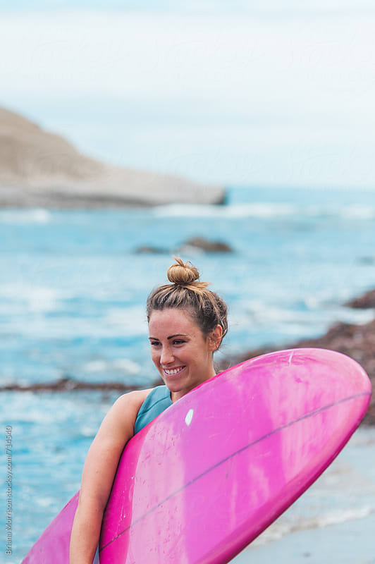 Happy Young Woman Surfer with A Pink Surfboard by Briana Morrison for Stocksy United