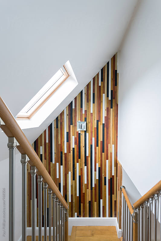 Multi coloured wood slat wall at the end of a contemporary staircase. by Paul Phillips for Stocksy United