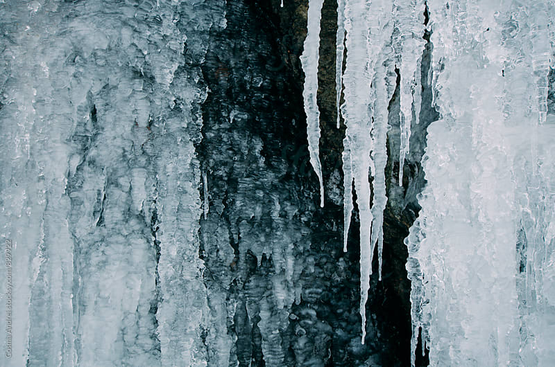 Icicles on frozen waterfall by Cosma Andrei for Stocksy United