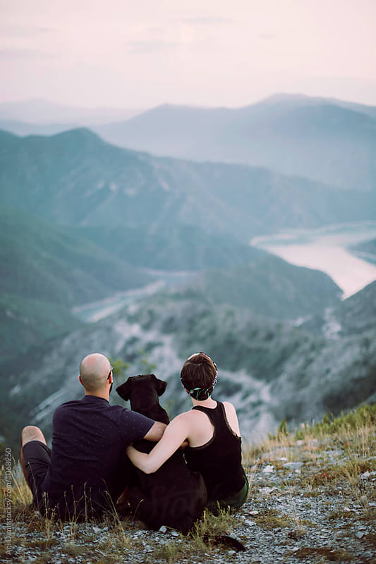 Couple sitting at a mountain top with their dog by Ani Dimi for Stocksy United