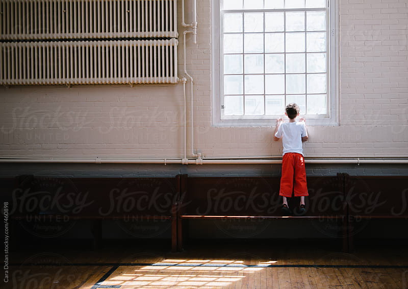 Boy looks out the window of an old building by Cara Dolan for Stocksy United