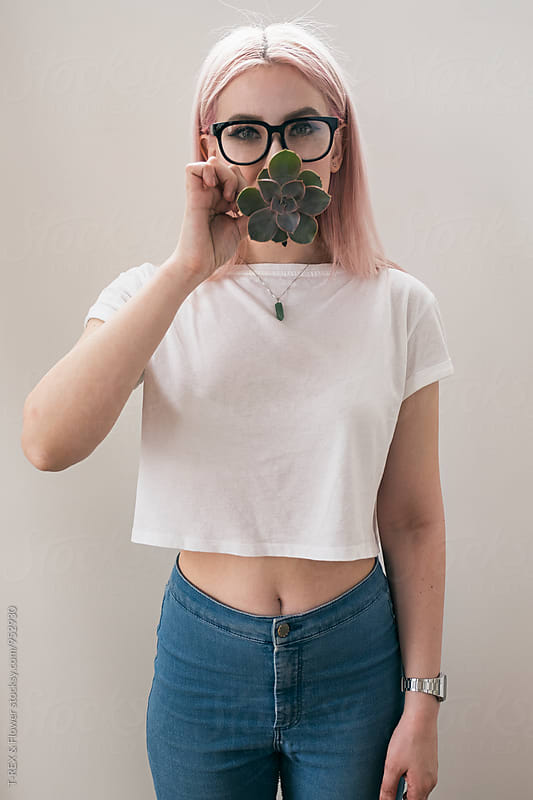 Blonde woman covering mouth with succulent by T-REX & Flower for Stocksy United
