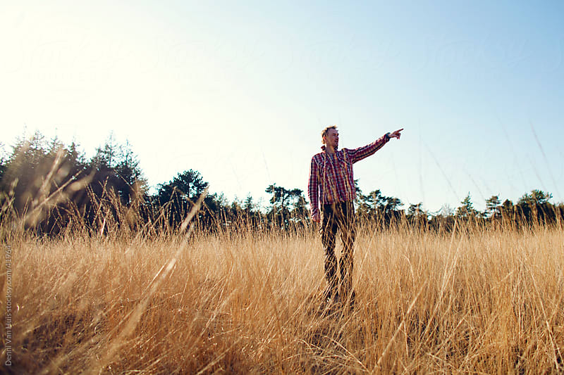Man standing in high grass pointing at something by Denni Van Huis for Stocksy United