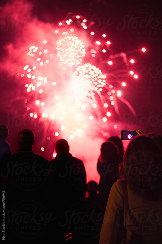Young woman taking a photo of fireworks by Pixel Stories for Stocksy United