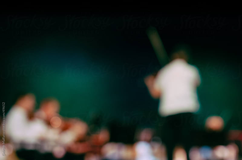 A conductor holding a violin leads a string orchestra, intentionally blurred by Deirdre Malfatto for Stocksy United