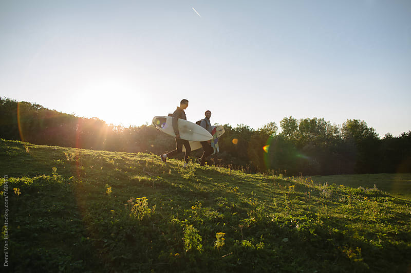 Friends hike through the dunes with surfboards in search of waves by Denni Van Huis for Stocksy United