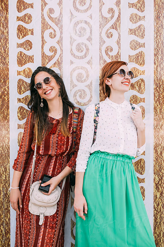 Two female friends smiling outdoors by Maja Topcagic for Stocksy United
