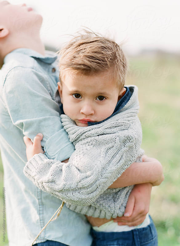 Boy being held by his brother by Marta Locklear for Stocksy United