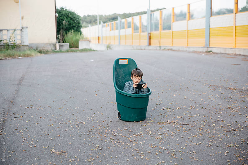Boy sitting in a barrow playing with a smartphone forgotten in the middle of the asphalt  by Beatrix Boros for Stocksy United