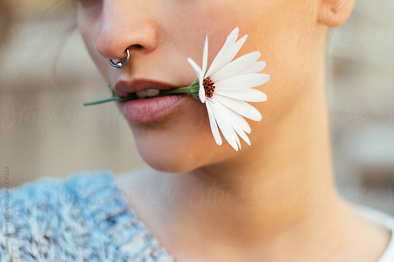 Detail: woman with daisy in mouth by Susana Ramírez for Stocksy United