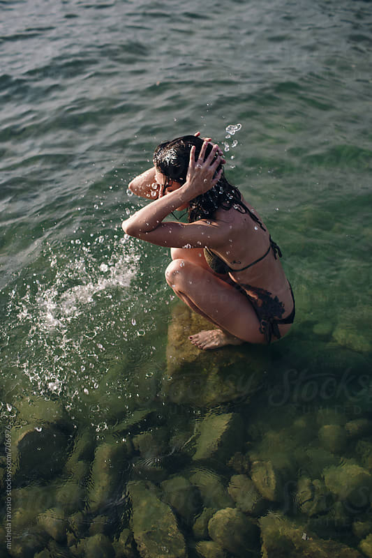Young woman refreshing herself at the lake by michela ravasio for Stocksy United