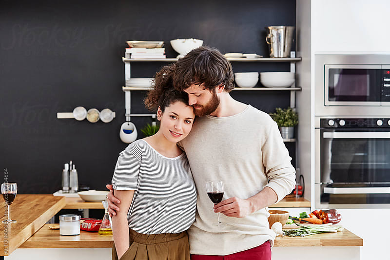 Loving Couple Holding Wineglass In Kitchen by ALTO IMAGES for Stocksy United