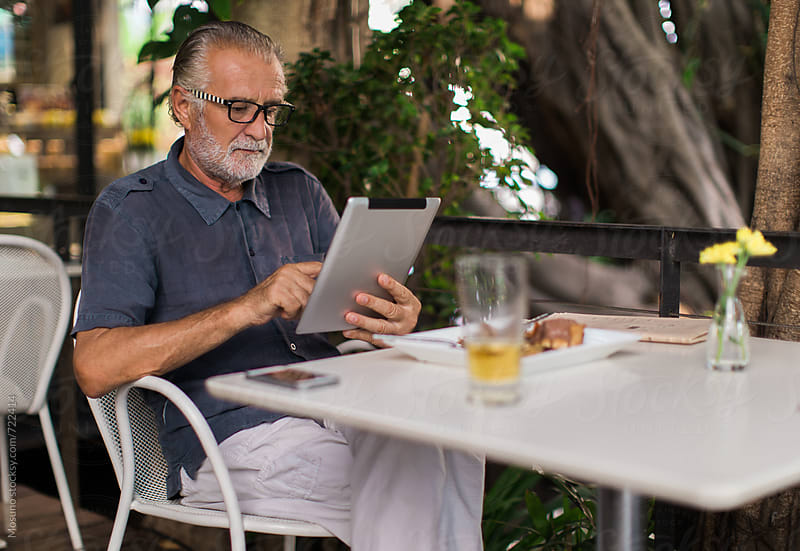 Older Man Using Computer in a Cafe by Mosuno for Stocksy United