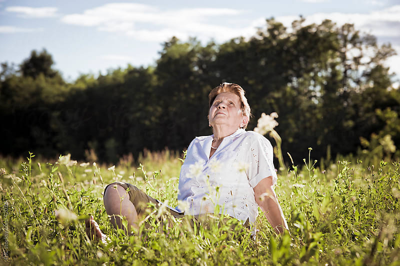 Senior woman relaxing sitting in a field by WAVE for Stocksy United