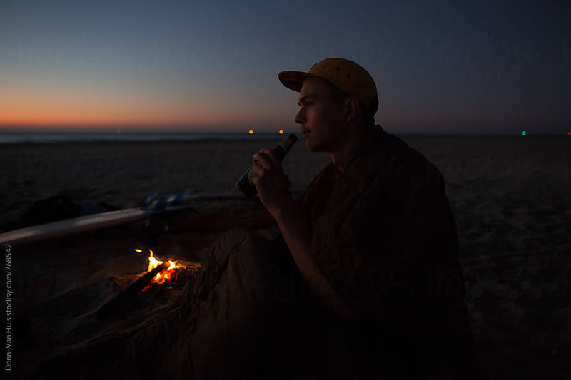 Man drinking on a beach at night by Denni Van Huis for Stocksy United