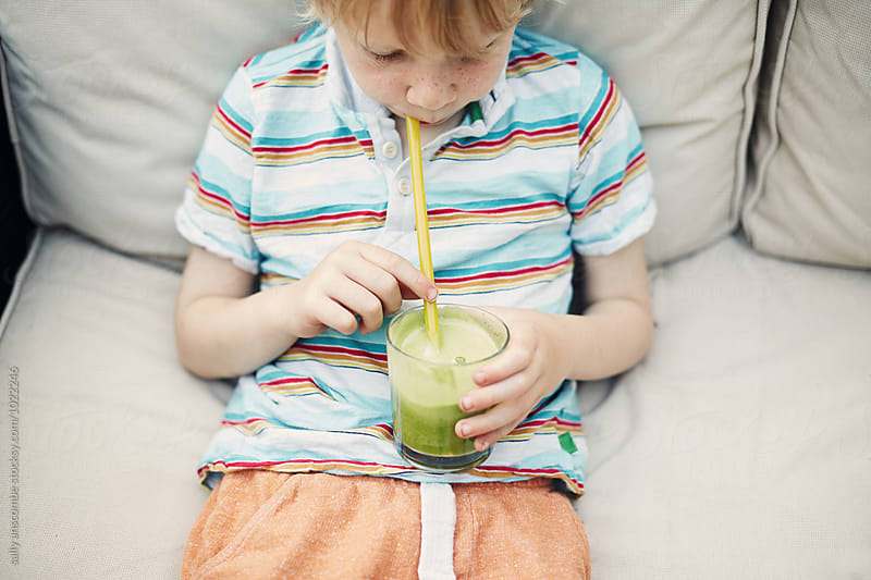 Child drinking a green smoothie by sally anscombe for Stocksy United