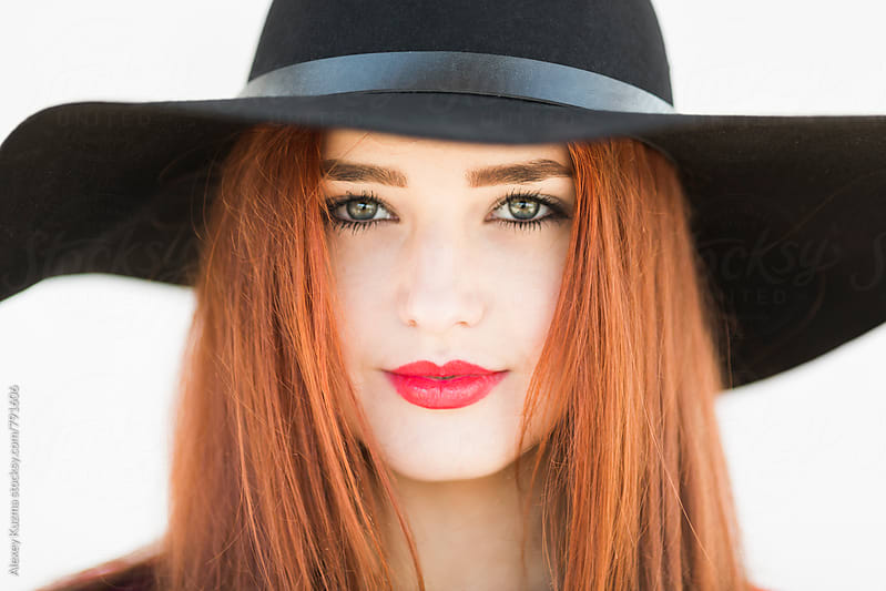 portrait of cool young woman with black hat on the white background by Alexey Kuzma for Stocksy United