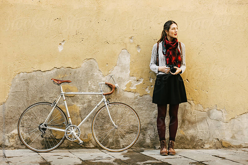 Chic woman standing beside her vintage bicycle in front of a wall. by BONNINSTUDIO for Stocksy United