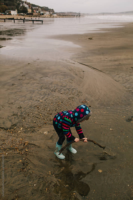 Little girl tries to dig hole in wet sand on wintry beach. by Julia Forsman for Stocksy United