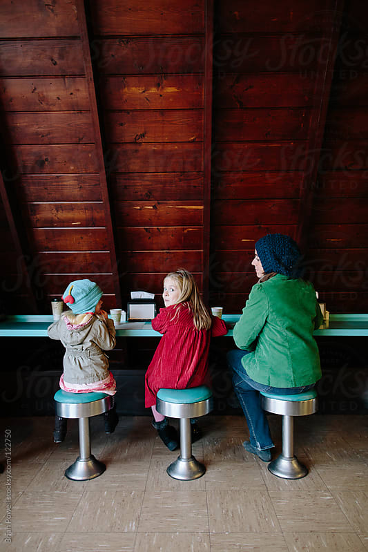 mom and kids at donut shop by Brian Powell for Stocksy United