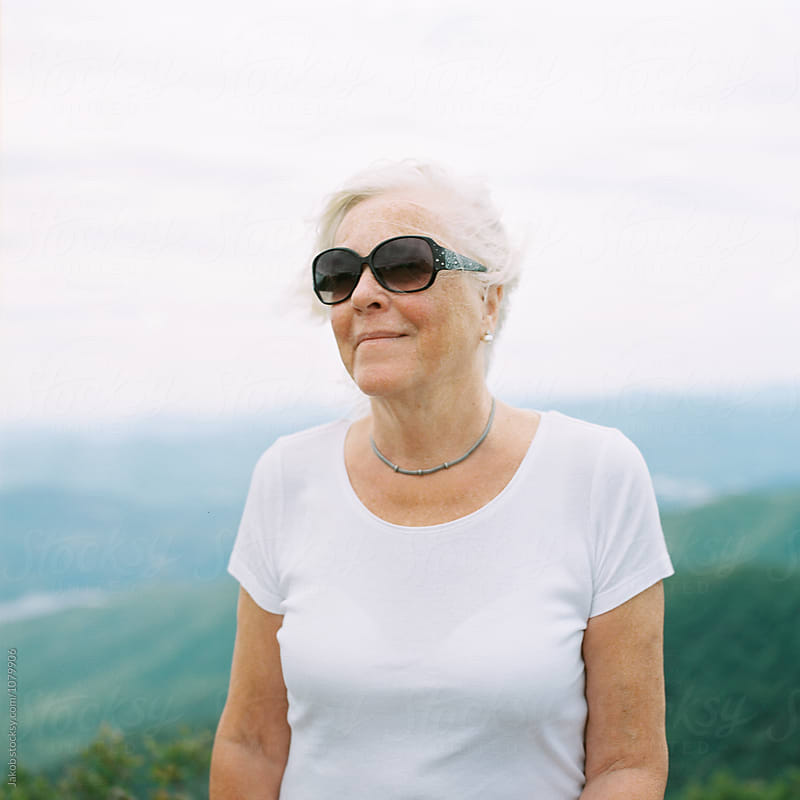 Portrait of an older woman with wind blowing in her face on top of a mountain by Jakob for Stocksy United