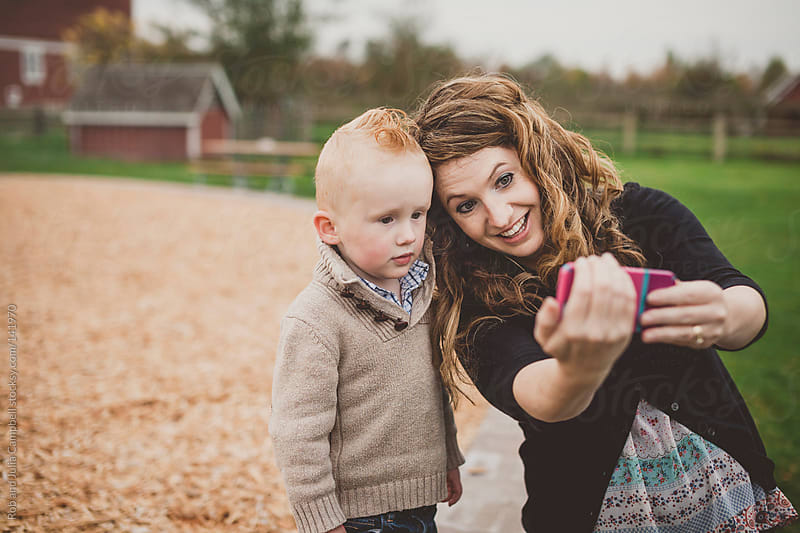 Beautiful young mother showing toddler her cell phone by Rob and Julia Campbell for Stocksy United