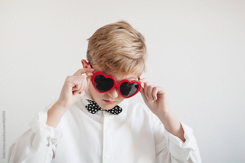 serious boy wearing heart shaped sunglasses by Kelly Knox for Stocksy United
