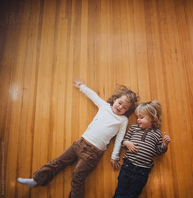 Two sisters lying on wood floor cuddling by Rob and Julia Campbell for Stocksy United