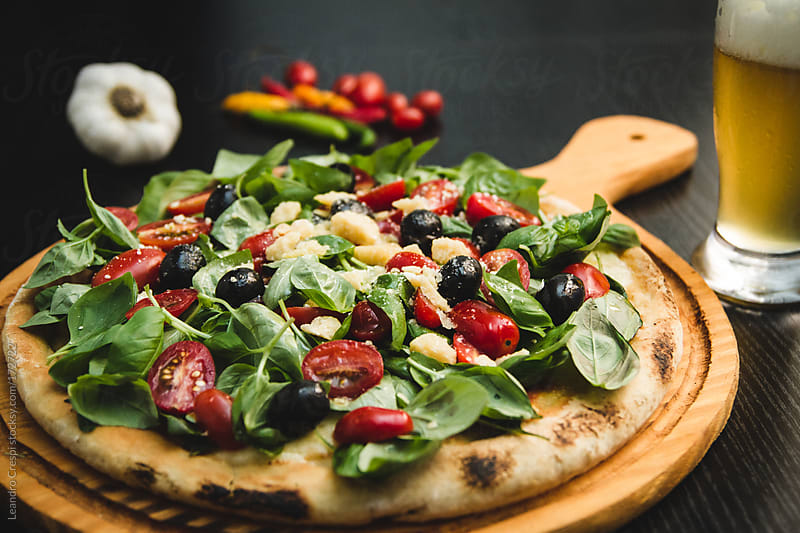 Vegetable pizza, tomatoe, peppers, beer by Leandro Crespi for Stocksy United