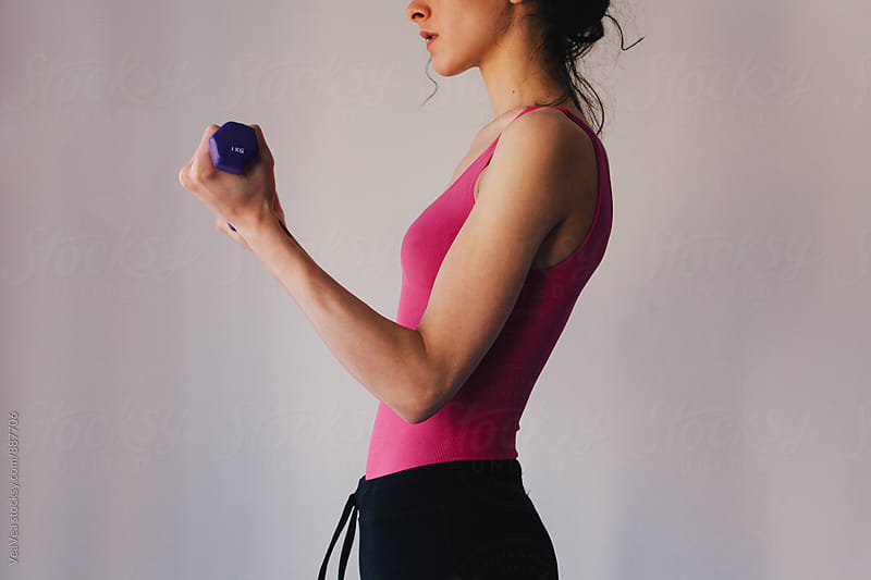 Woman in sportswear holding a set of weights  by Marija Mandic for Stocksy United