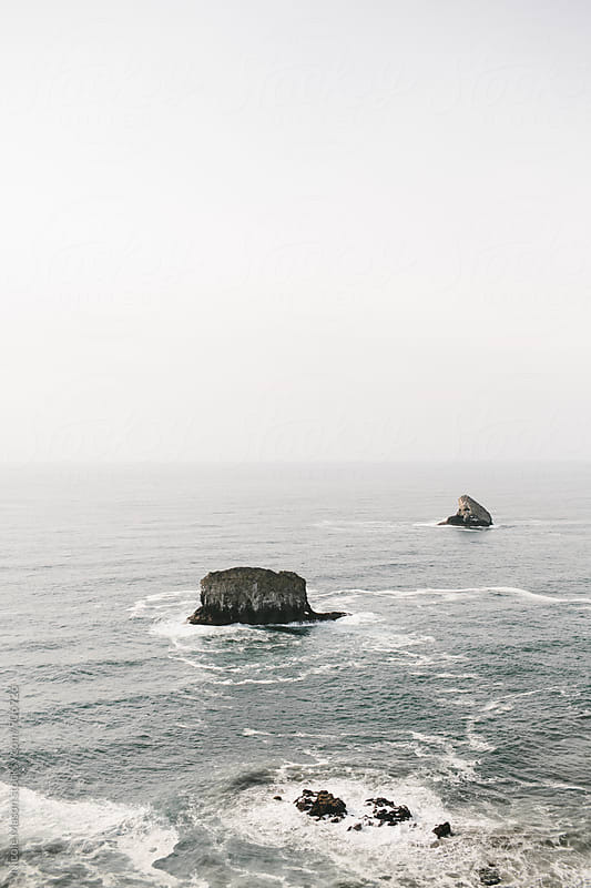 ocean near coast with two large rocks by Nicole Mason for Stocksy United