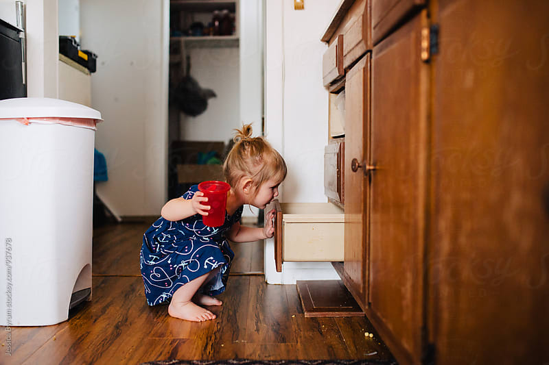 Little girl holding cup looking in drawer by Jessica Byrum for Stocksy United