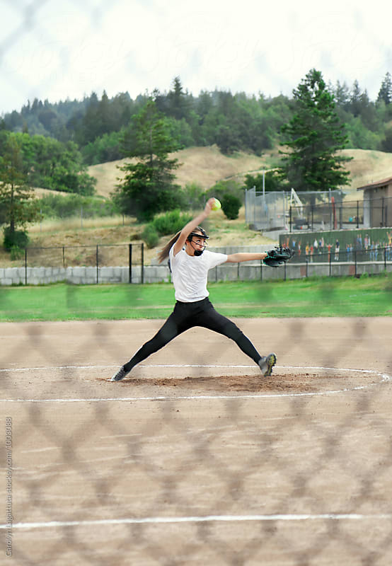 Teenage girl pitching in a fast pitch softball game by Carolyn Lagattuta for Stocksy United