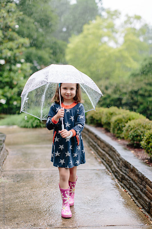 Cute young girl walking in the rain with an umbrella by Jakob for Stocksy United