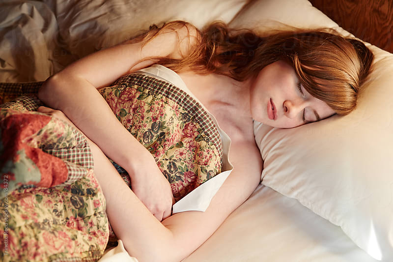 Redhead young woman sleeping in bed at home by Trinette Reed for Stocksy United