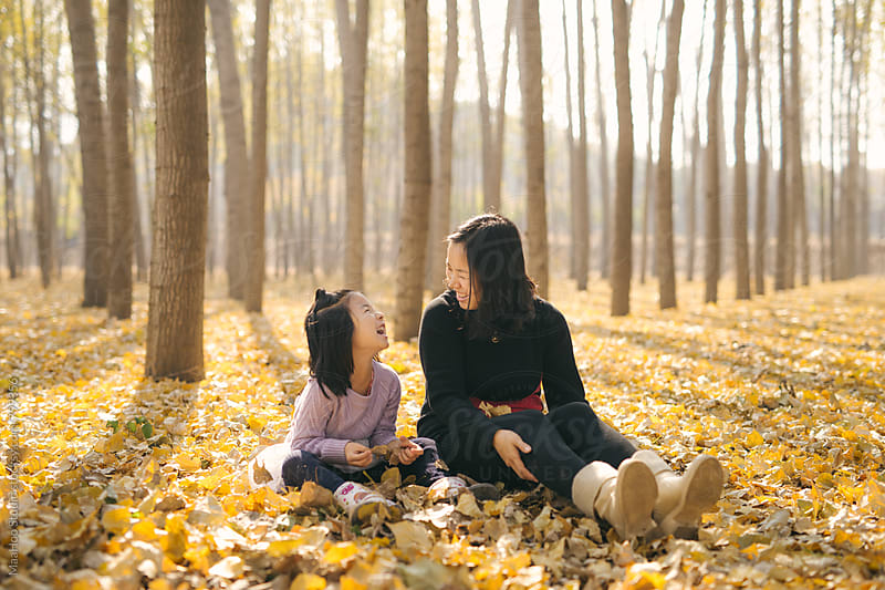 Young mother and daughter playing in autumn wood by Maa Hoo for Stocksy United