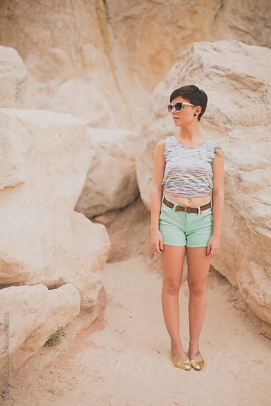 Girl in sunglasses standing in the sand by rocks by Gabrielle Lutze for Stocksy United