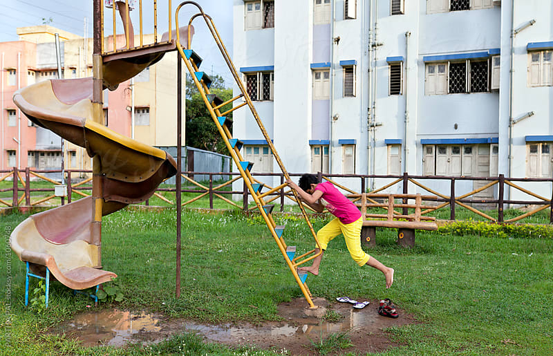 A girl climbing the upstairs of a Slip in park by PARTHA PAL for Stocksy United