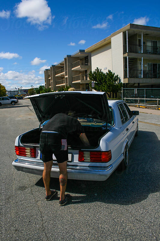 Hip young man digs in back of car trunk by Peyton Weikert for Stocksy United