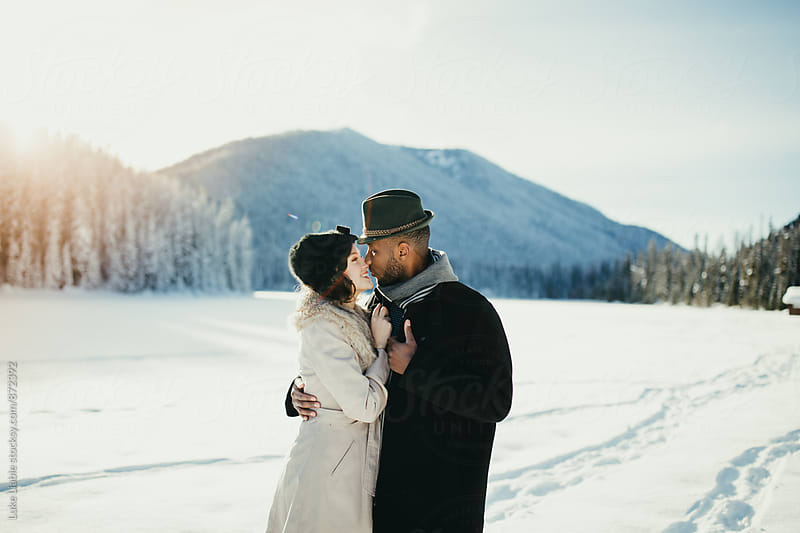 Young mixed couple embrace in love on snow covered winter lake by Luke Liable for Stocksy United