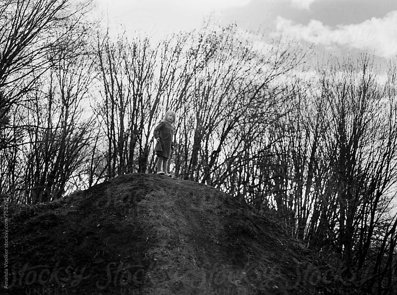 Young Girl Stands Alone at the top of a hill by Amanda Voelker for Stocksy United