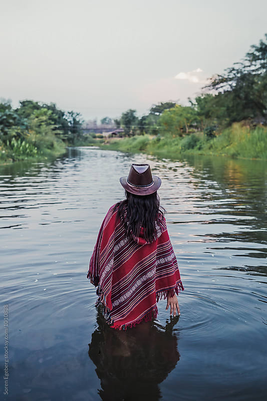 Woman walking in river wearing a red poncho and hat by Søren Egeberg Photography for Stocksy United