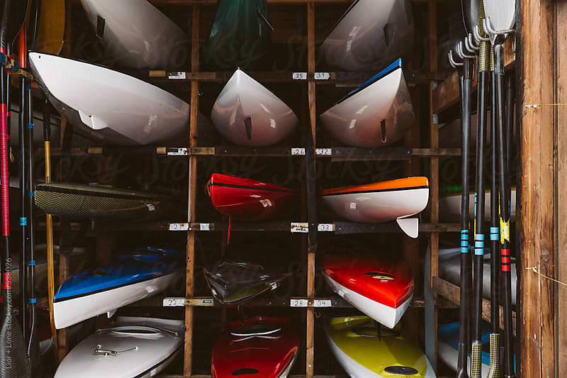 Kayaks and paddles in storage facility by Lior + Lone for Stocksy United