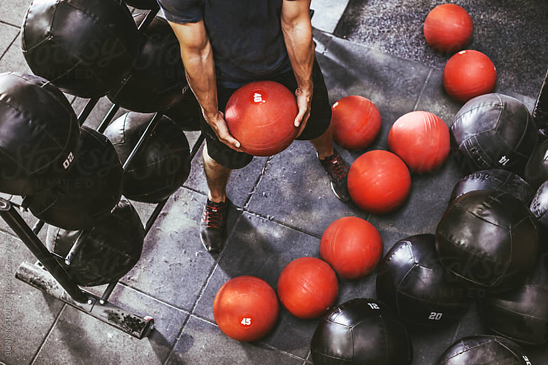 Anonymous man lifting a red weighted ball in a gym. by BONNINSTUDIO for Stocksy United