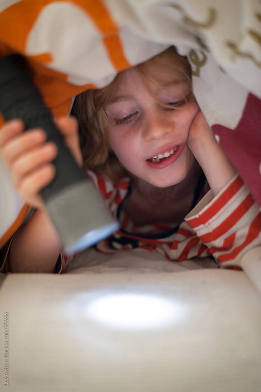 boy reading in bed by flashlight by Lee Avison for Stocksy United