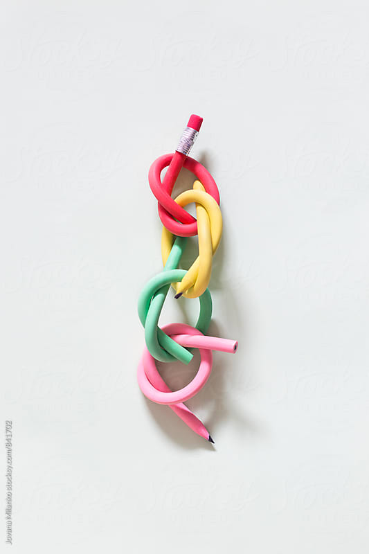 Colorful pencils tied in knots, making a chane with eraser on one and sharp pencil on the other end by Jovana Milanko for Stocksy United
