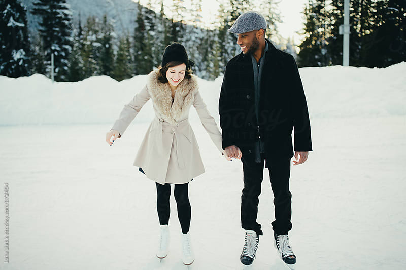 Mixed race couple laughing while skating on snow pond by Luke Liable for Stocksy United