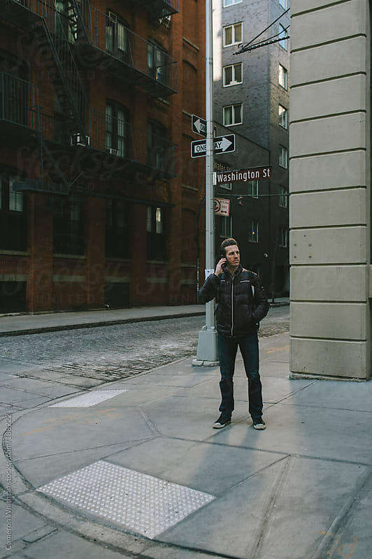 Man talking on cellphone at a street corner  by Cameron Whitman for Stocksy United